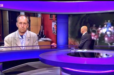 Peter Dennis, chairman of the British Cave Rescue Council, is interviewed on BBC's Newsnight by Evan Davis, with John Volanthen's images of the stranded boys in the background.